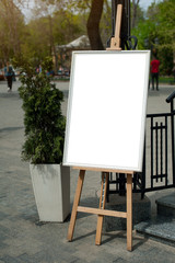 Mock up - painting on an easel in a city. Vertical photo.