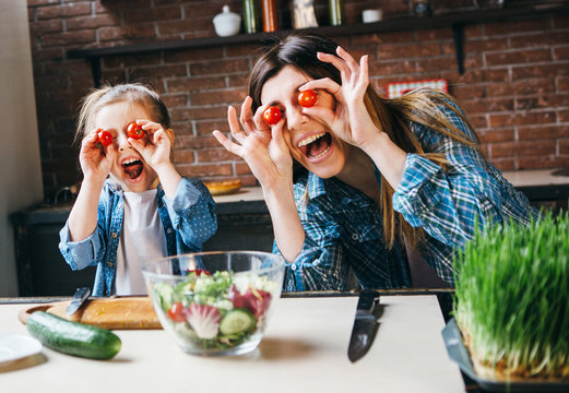 Mother cook with daughter on kitchen,take fun with tomatoes.