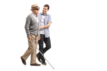 Blind mature man walking with the help of a young man