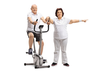 Mature man riding a stationary bike with a mature woman pointing