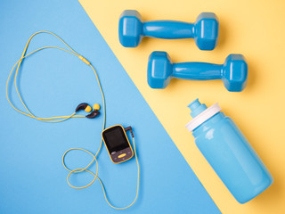 Photo of player, dumbbells, bottle of water on blue and yellow background