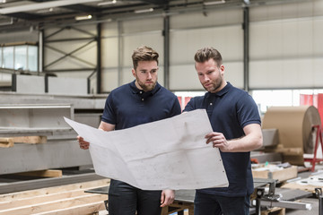 Two men looking at plan in factory Wall mural