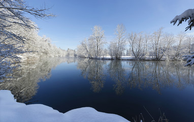 Trees reflected in Loisach River in winter