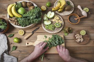 Man preparing green smoothie cutting kale