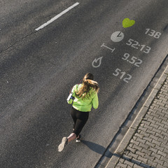 Young woman running on a street with data