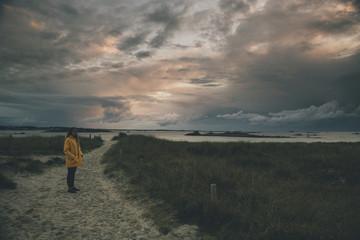 France, Brittany, Landeda, Dunes de Sainte-Marguerite, young woman standing in dune at dusk