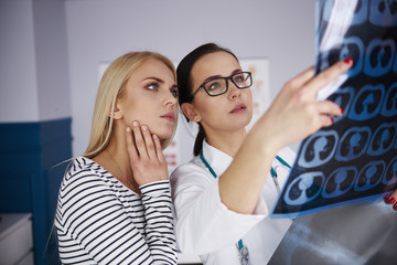 Doctor showing x-ray to young woman