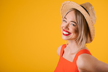 Happy blonde woamn in straw hat and fancy red dress. Bright summer yellow and red colors. Vacation mood