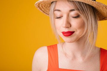 Beautiful blonde woman in straw hat. Closed eyes. Yellow summer mood background. pensive dreamy face