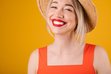 Happy adorable blonde woman with big tetty smile and straw hat. Warm summer background. Bright yellow and red summer colors