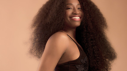 Beauty mixed race african american woman with hair blowed in air smiling at camera