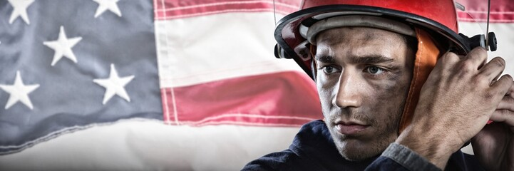Composite image of serious fireman putting on helmet
