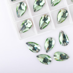 Precious stones green color in the pallet on a white background.