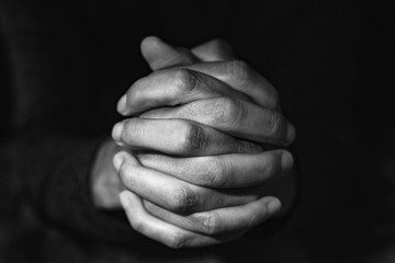 man with his hands clasped, in black and white