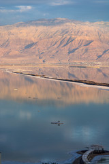 Landscape with reflection, sunset over lowest salty lake in world below sea level Dead sea, full of minerals near luxury vacation resort Ein Bokek, perfect place for medical treatments.
