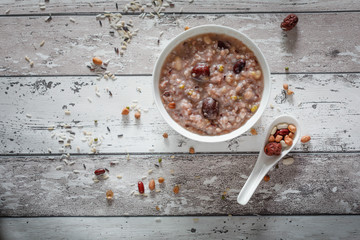 Eight Treasure Congee on traditional chinese festive porridge, mixed from eight ingredients: red beans, lotus seeds, peanuts, dates, pine nuts, lily, almond and walnut on white wooden table, top view