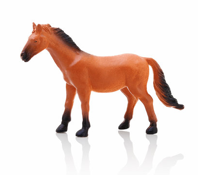 Children´s small plastic brown - black horse isolated on the white background with shadow reflection. Small childish toy in the shape of horse. Miniature of brown horse on white background with shadow