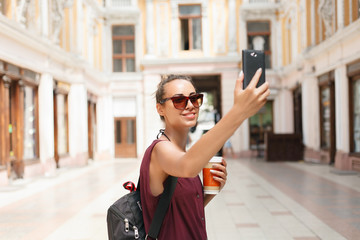 Portrait of beautiful young tourist woman holding up a smartphone taking selfies pictures of herself, networking on line. Travel, technology and lifestyle outdoors. Woman using a smart phone device.
