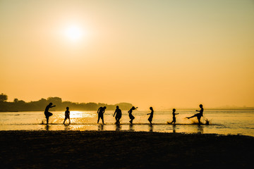 Silhouette of children playing water with friend