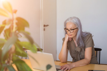 Mature woman working with computer while sitting at desk