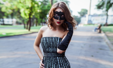 A young and beautiful woman dressed in a striped cocktail black and white dress, black gloves and a black mask on her face, stands in the park against the background of green trees.