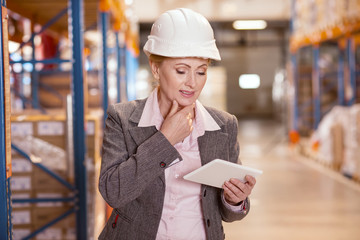 Electronic device. Nice pleasant woman looking at her tablet while working as a storehouse manager
