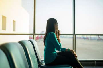 Asian woman passenger using smartphone and checking flight or online check in and travel planner at international airport