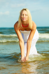 Blonde woman wearing dress playing with water