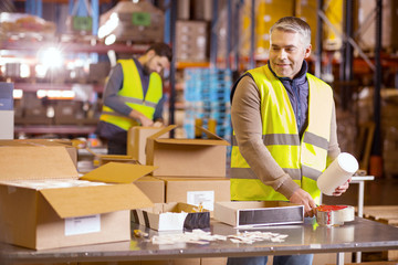 Manual job. Nice hard working man standing at the table and preparing the package