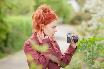 Beautiful young woman with red hair in the garden taking pictures with old, analog camera