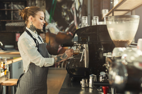 Tattooed barista making coffee in professional coffee machine