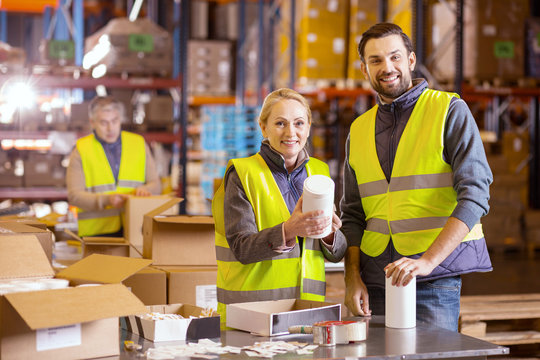 Wholesale retail. Joyful positive people looking at you while working in the wholesale retail industry