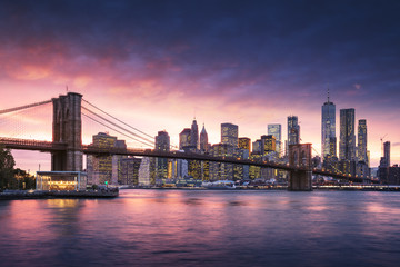 Fototapete - Famous Brooklyn Bridge in New York City with financial district - downtown Manhattan in background. Sightseeing boat on the East River and beautiful sunset over Jane's Carousel.
