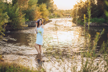 Young beautiful drowned woman in blue dress staying in the water at the lake. Fairy tale woman story. Sunset. Girl in flowers wreath.