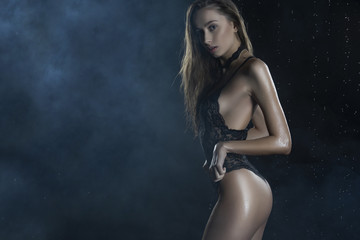 Beautiful young wet slim girl wearing a black lingerie poses in rain water drops and shows her beautiful butt in a studio on black background in a theatrical smoke