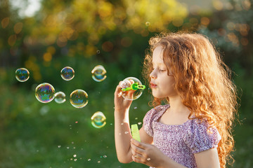 Little curly girl blowing soap bubbles.