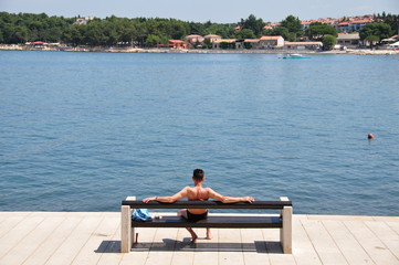 Raucher sitzt auf einer Bank am Meer