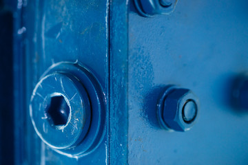 Blue metal rough surface of part with bolts and nuts. Blue painted of auto part. Automotive grunge background image.