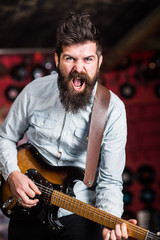 Rock music concept. Musician with beard play electric guitar. Talented musician, soloist, singer play guitar in music club on background. Man with shouting face play guitar, singing song, play music.
