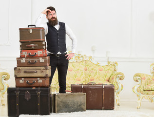 Baggage and relocation concept. Man with beard and mustache packed luggage, white interior background. Macho elegant on tired face, exhausted at end of packing, leans on pile of vintage suitcases.