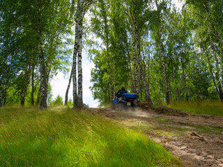 Sunny summer wood. A man on ATV is getting up a high hill.
