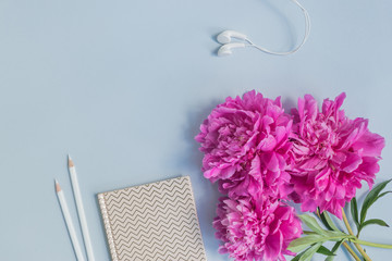 Flat lay desk with pink peonies, notebook and accessories