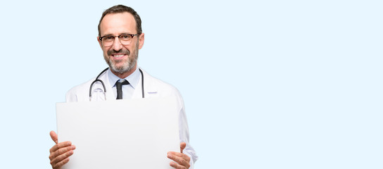 Doctor senior man, medical professional holding blank advertising banner, good poster for ad, offer or announcement, big paper billboard isolated over blue background