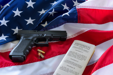 The second amendment and gun control in the US, concept. Handgun, bullets, and the american constitution on the USA flag.
