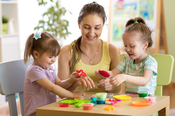 Children and their mom playing colorful clay toy