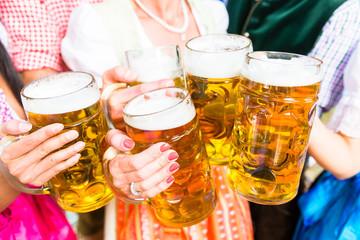 Anstoßen mit Bier in Maßkrügen im Biergarten