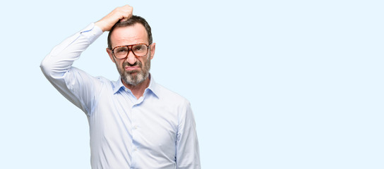 Middle age man with glasses doubt expression, confuse and wonder concept, uncertain future isolated over blue background