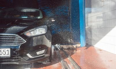 Auto in der Waschanlage, die Felgen werden gewaschen