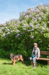 frau sitzt mit hund in natur unter einem fliederstrauch