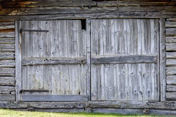 Old gray traditional wooden door with cross